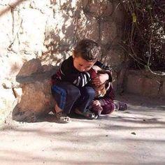 suriyede küçük kızkardeşini bombalardan korumaya çalışan küçük bir abi.