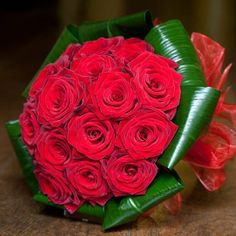 Hand-tied bouquet of grand prix roses and aspidistra leaves. Bound with red organza ribbon