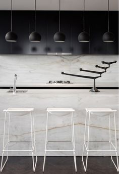 12 Kitchen Counters: The Calacatta marble used in this kitchen has prominent gold veins, adding color to the black and white palette. This unit, as well as the entire building, 33 Mackenzie Tower in Melbourne, was designed by architects Callum Fraser and Zahava Elenberg of Elenberg Fraser.