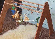 DIY Wooden Play Gym for less than $30! It looks nicer, feels nicer, and it is much classier than your average infant toy gym.