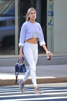 Hailey Baldwin wearing Ethan K Alla Bag, Yeezy Boost 350 V2 Sneakers, Are You Am I Ava Cropped Sweater and Alo Yoga Moto Leggings in Vapor Grey