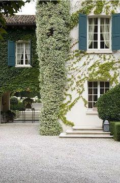 White stucco, white windows, teal shutters, tile roof, pale grey pea gravel, jasmine. Lovely!