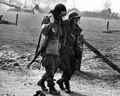 An American paratrooper of the 17th Airborne Division helps his buddy after landing in Germany, 1945. #WW2