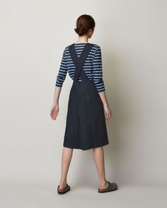 Pinafore front dress in deep, indigo-dyed denim. Slanted patch pockets. Wide…