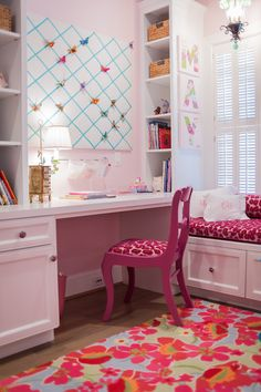 Janet Gust Interiors - Adorable girl's room with pink walls accented by a ribbon trimmed memo board in between built-in bookcases over a built-in desk lined with a fuchsia pink desk chair. The bedroom features a storage window seat topped with a pink velvet seat cushion as well as a pair of monogrammed pillows in front of plantation shuttered windows over hardwood floors layered with a bright floral print rug.