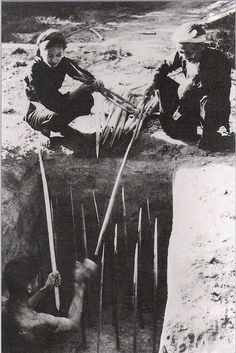 Viet Cong guerrillas laying punji trap near Cu Chi.