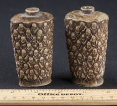LOT OF TWO MATCHING MINIATURE NETSUKE LIKE VASES WITH DOZENS OF FACES MOLDED INTO THEM. MEASURES 3 INCHES TALL