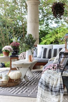 gorgeous fall porch with neutral pillows and blankets and pastel mums and pumpkins