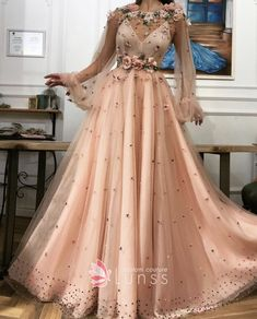 Peach nude color A-line evening special occasion dress with long sleeves, V neckline, tulle fabric overlay, handmade embroideries pearls, flowers, diamond crystals, and unique flowery belt details.