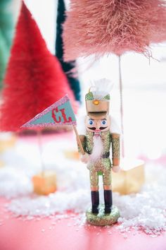 A whimsical Christmas table setting by coco+kelley complete with bottlebrush trees, pink souffles, glittering nutcrackers and a sprinkle of snow. Pink Christmas Tree, Christmas Decorations For The Home, Whimsical Christmas, Christmas Table Settings, Nutcracker Christmas, Merry Little Christmas, Noel Christmas, Winter Christmas, Vintage Christmas