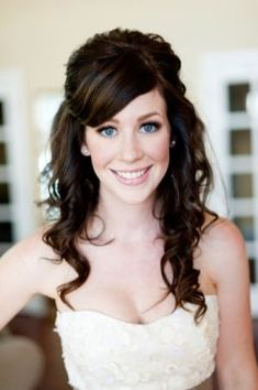 Half up wedding hairstyle with side swept bangs.