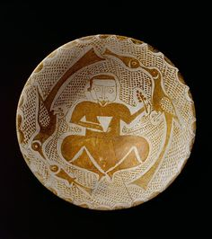 Luster ceramics from Samarra often include stylized human figures. In this example, the lively caricatural quality of the seated man holding a cup and a flowering branch is enhanced by the two birds that hold fish in their beaks but look like they are kissing