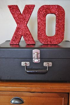This past weekend I was browsing through the craft store when I saw those plain, cardboard letters. I wanted to make them into decorations for Valentine's Day, so I bought an X and an O, and some….  glitter!! I turned those plain boring letters into super sparkly shimmering shining holiday decor. And you can …