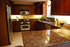 Yellow walls, cherry cupboards, brown counter, tan floor, stainless. Makes the room look small ~!~