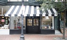 My dream shop - black and white awning, two large windows for display, black doors and even a brick sidewalk!