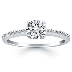 Slender and graceful, this demure ring is accented by sparkling pave diamonds set along the front of the band. The center highlights a sparkling 1/2 carat round cut diamond.