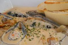 Mussels in creamy garlic sauce  3 lbs fresh mussels, well scrubbed  1/4 cup butter  1/2 cup good chicken stock  1/2 cup chopped celery  2 carrots, diced  1 medium white onion, chopped  2 cloves minced garlic  1/2 tsp dried thyme  1 bay leaf  1/2 cup whitewine  2 tbsp chopped parsley  1 cup heavy cream  salt & pepper to taste  squeeze of fresh lemon juice