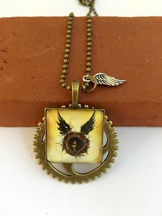 To celebrate the arrival of Harry Potter & the Cursed Child, this bronze pendant is set on a brushed bronze steampunk gear and placed on a bronze ball chain, and adorned with a small silver wing.