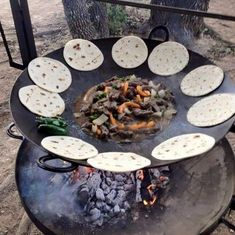 """""""Discada"""" or """"Cowboy Cooker"""" made from plow discs with the center hole welded closed and horse shoes welded on for handles."""