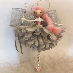 Meet Miss Annabelle, a beautiful handcrafted fairy doll that will adorn any room in your home! She is approximately 10 inches tall from the tip of her toes to the top of her head and hangs from a silver thread. She wears a petal dress in a soft dove grey, with a pink bodice decorated