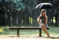 Françoise Hardy Sitting Pretty On A Bench With An Umbrella On A Rainy Day