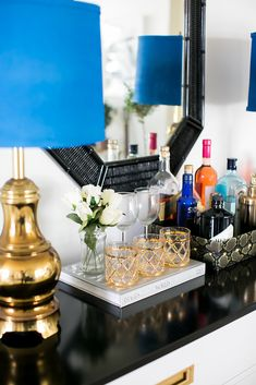 Home bar ideas for small spaces. Domino shares tiny little bars and bar ideas for a holiday party in your studio apartment! Read on for tiny home bar inspiration you can create in your own spirited space. For more home bar ideas go to Domino. Bar Cart Styling, Bar Cart Decor, Styling Tips, Home Design, Tops Diy, Bandeja Bar, Los Angeles Apartments, Blue Lamp Shade, Lamp Shades