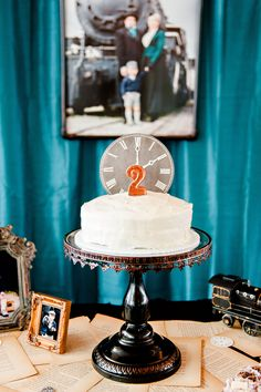 "Black metal cake stand with copper paint accents. Clock face cake topper with copper painted ""2"" candle."