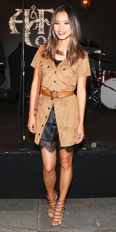 At an Abercrombie & Fitch summer rooftop party, Jamie Chung gives us serious safari vibes in a tan button-down shirtdress—effortlessly belted over a black, negligee-inspired slip—strappy sandals, and purse. A gold collar necklace beautiful picks up the outfit's warm undertones.