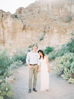 Couple strolls through desert pathway hand-in hand. Outdoor engagement.  - Melissa Jill Photography