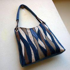 džíska vlnkovaná Nr.3 Větší kabelka je ušitá ze světle modré recydžínoviny. Přední strana je kompozicí krásně strukturovaných materiálů v odstínech modré, režné a hnědé, doplněnou zajímavě probarvenými kousky modré džínoviny. Kabelka je pečlivě podlepená, pěkně drží tvar. Podšívka z džínoviny má 6 kapes, z nich dvě uzavíratelné na zip. Kabelka je ...