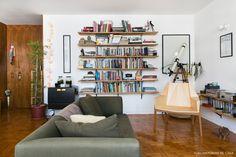 Sala de estar de apê alugado tem prateleiras de madeira sustentadas por mão francesa.