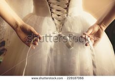 Closeup toned photo of beautiful bride tying up her wedding dress - stock photo
