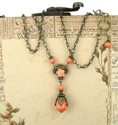 To make this vintage-inspired, neo Victorian style necklace, I used coral-hued Swarovski crystal pearls and antiqued brass. The focal is a teardrop