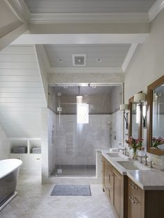 """With their stunning yet subtle color variation, the cream-and-gray Waterworks Keystone tiles—used in squares in the shower and in a chevron pattern on the floor—deliver a graphic visual impact. """"With the chevron pattern, you have a lot of grout lines, which creates more traction to minimize slipping,"""" Chambers says. Polished nickel—in the form of fixtures by Waterworks and Evasion sconces by Jean De Merry—adds a bit of sheen to the room."""