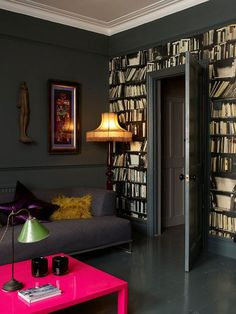 dark and moody + wall of books +hot pink table I would usually hate but i love it in this room