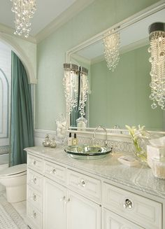 The bathroom shimmers with glass beaded wallpaper, hung above a marble wainscot  The vanity features a mirroredglass vessel sink and spherical glass knobs backed by mirrored plates  Lighting is sconces and a dramatic ceiling fixture of crystal strands   Bath  Transitional by Sherry Hayslip Interiors & Hayslip Design Associates, Inc