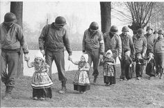 American soldiers escort a group of Dutch children dressed up in traditional costume for a concert after the liberation in February, 1945