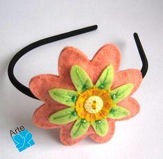 Tiara com flor em feltro bordado, com aplicação de botão e contas.  Diâmetro: 8,0 cm.  Fino acabamento... R$ 30,00