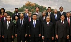 China's President Xi Jinping poses for photos with guests at the Asian Infrastructure Investment Bank launch ceremony at the Great Hall of the...