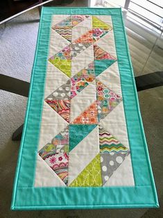 This a a pretty table runner that will grace your table or side table with a festive Spring or Easter look. I call it the Spring Ribbon Table Runner and it measures 37 x 16 1/2 and is made of 100% cotton. The front features Spring colors of turquoise, pink, tangerine, lime green,