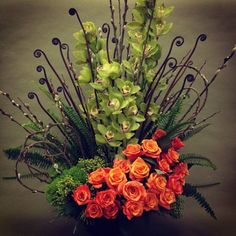 fiddleheads, pussy willow cymbidium orchids, orange roses, modern