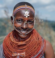 Samburu girls are given strings of beads by their fathers when they are still young. As soon as they are old enough to have lovers from the warrior age-set, they regularly receive gifts from them. Over a period of years, their necklaces can smother them up to their necks. The metal cross-like ornament hanging from the girlユs headband has no religious significance. Only girls and warriors decorate their faces with abstract designs; the orange powder they use for this purpose is called メblueモ!