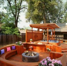 A deck with a fire pit with plenty of seating, a hot tub with a pergola, and a privacy wall blocking the hot tub off from neighboring eyes. Fantastic!