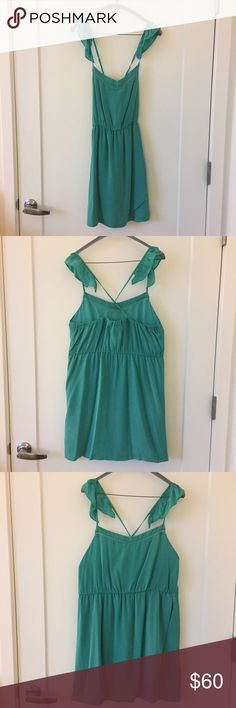 Silk teal dress Silk dress has adjustable spaghetti straps that have flutter sleeves and cross in back. Skirt has flap in front for faux-wrap style. Greylin Dresses Mini