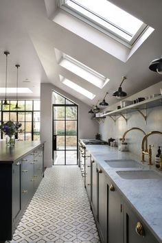 Clean kitchen with sloped ceiling with skylights and interesting tile floor