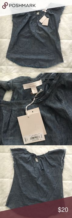 Lauren Conrad denim shirt NWT. Lauren Conrad pleat neck woven top. Capped sleeves have frayed edges and the bottom of shirt also has frayed edges. Cute bow tie on top of back side of the shirt. LC Lauren Conrad Tops