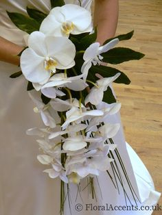Elegant bridal shower bouquet of white Phalaenopsis orchids, tropical leaves and iridescent beads threaded on steel grass.