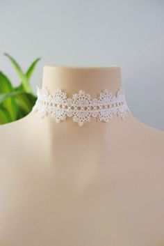 This white choker features a wide crocheted band with a stylized design…