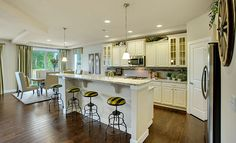 This kitchen from @Lennar Seattle features classic white cabinets and wood floors