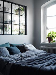 Indoor window between bedroom and kitchen and blue linen